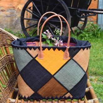 Vævet/flettet net i sort, grå, varm gul og jordfarver og med handtag i svineskind. En rummelig taske med bindesnor, som lukker til for indholdet.