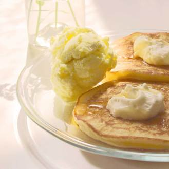 To lune amerikanske pandekager med to kugler is, flødeskumstoppe og sirup.