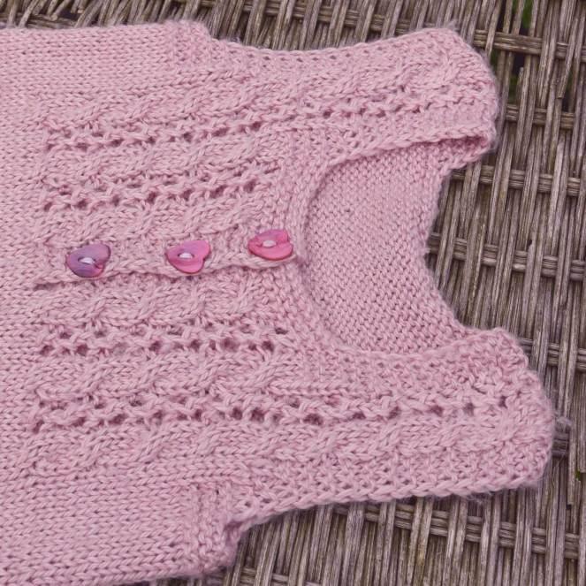 En strikket sartrosa baby-undertrøje med hulmønster og hjerteformede perlemorsknapper. I garnafdelingen har vi opskriften og garnet, som er af det blødeste bløde baby-alpaca.