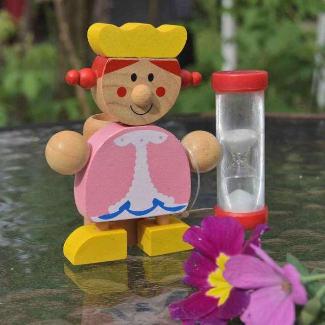 Et timeglas, som en smilende prinsesse står med i hånden. Princessen er lavet af malet træ og timeglasset af plastik.