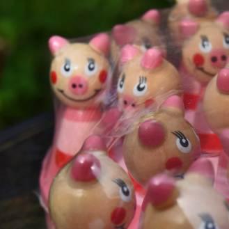 Solitairespil af træ malet i tøse-farver. Brikkerne, som man flytter med, er smilende grise i røde og pink kjoler, og selve brættet er udformet som et hjerte i samme farver.