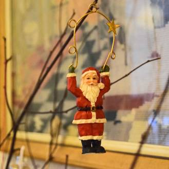 En julemand, der hænger i armene i en gylden bue, som for eksempel kan hænges på juletræet